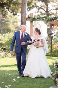 Father of the bride looks lovingly at his daughter as he walks her down the aisle at Mile High Oaks wedding