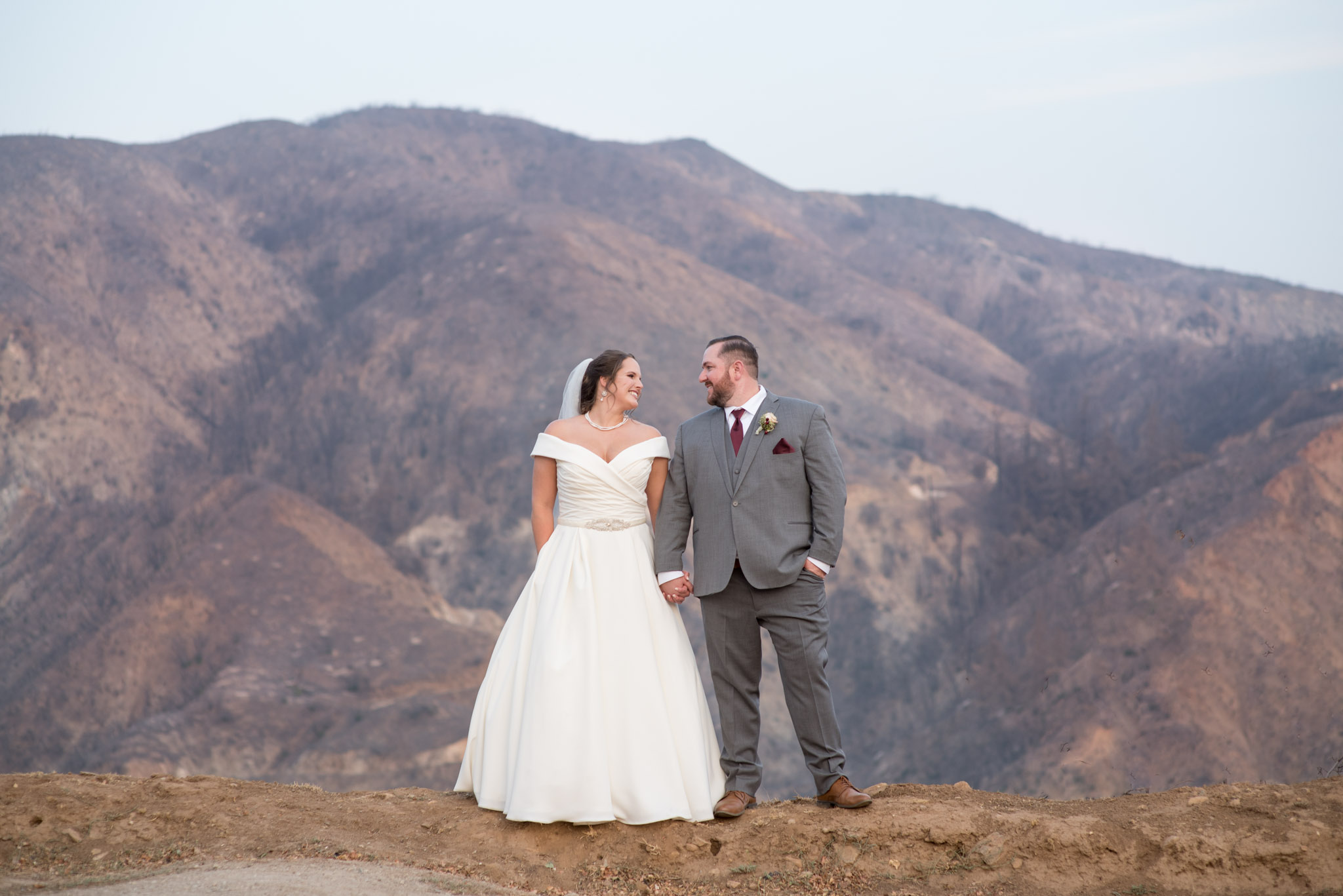 Bride and groom take portraits in front of San Bernardino Mountains at Mile High Oaks wedding