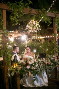 Bride and groom smile at each other during toasts at Mile High Oaks wedding