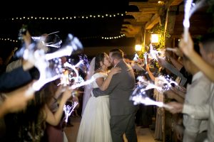 Bride and groom share a kiss during the grand exit at Mile High Oaks wedding