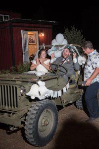 Bride and groom depart in a vintage Jeep at Mile High Oaks wedding