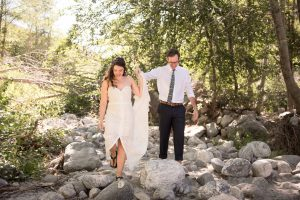 Bride and groom climb over rocks at their Thurman Flats elopement Southern California.