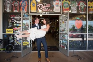 Groom picks up bride in front of Don's Bicycles in Redlands California
