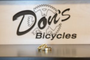 Bride and groom rings in front of Don's bicycle sign in Redlands California elopement
