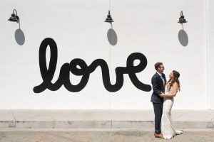 Bride and groom share a laugh in front of a mural in downtown Redlands wedding elopement