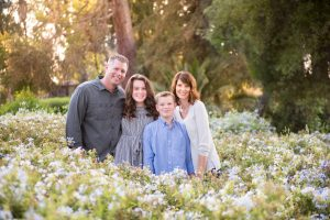 A dad, daughter, son, and mom all smile at the camera in a field of flowers in Prospect Park Redlands CA.