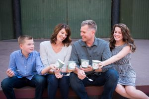 A son, mom, dad, and daughter cheers with cups of gelato. The family owns Happy Camper Creamery in Redlands CA