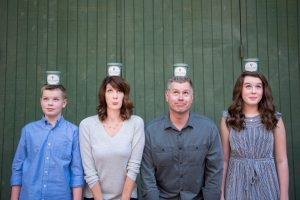 a son, mom, dad, and daughter balance Happy Camper Creamery cups of gelato on their heads. They are the owners of the company in Redlands CA.