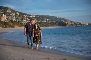 A man and woman are walking along the blue water, smiling at each other at Treasure Island Laguna Beach