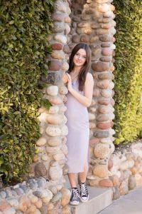 High School Senior peeks around the corner in La Jolla San Diego. She is wearing a long lavender dress.