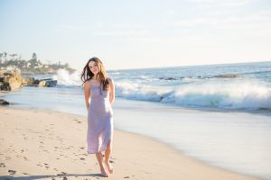 High school senior walks along Windansea beach in La Jolla. She is wearing a long lavender dress.
