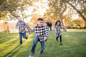Children in buffalo check shirts are running towards the photographer. It is fall in Yucaipa.