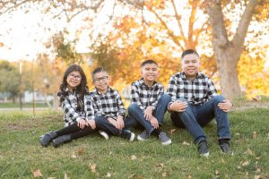 Family of 6 is all hugging each other, children are wearing buffalo check shirts. Background is fall colors.