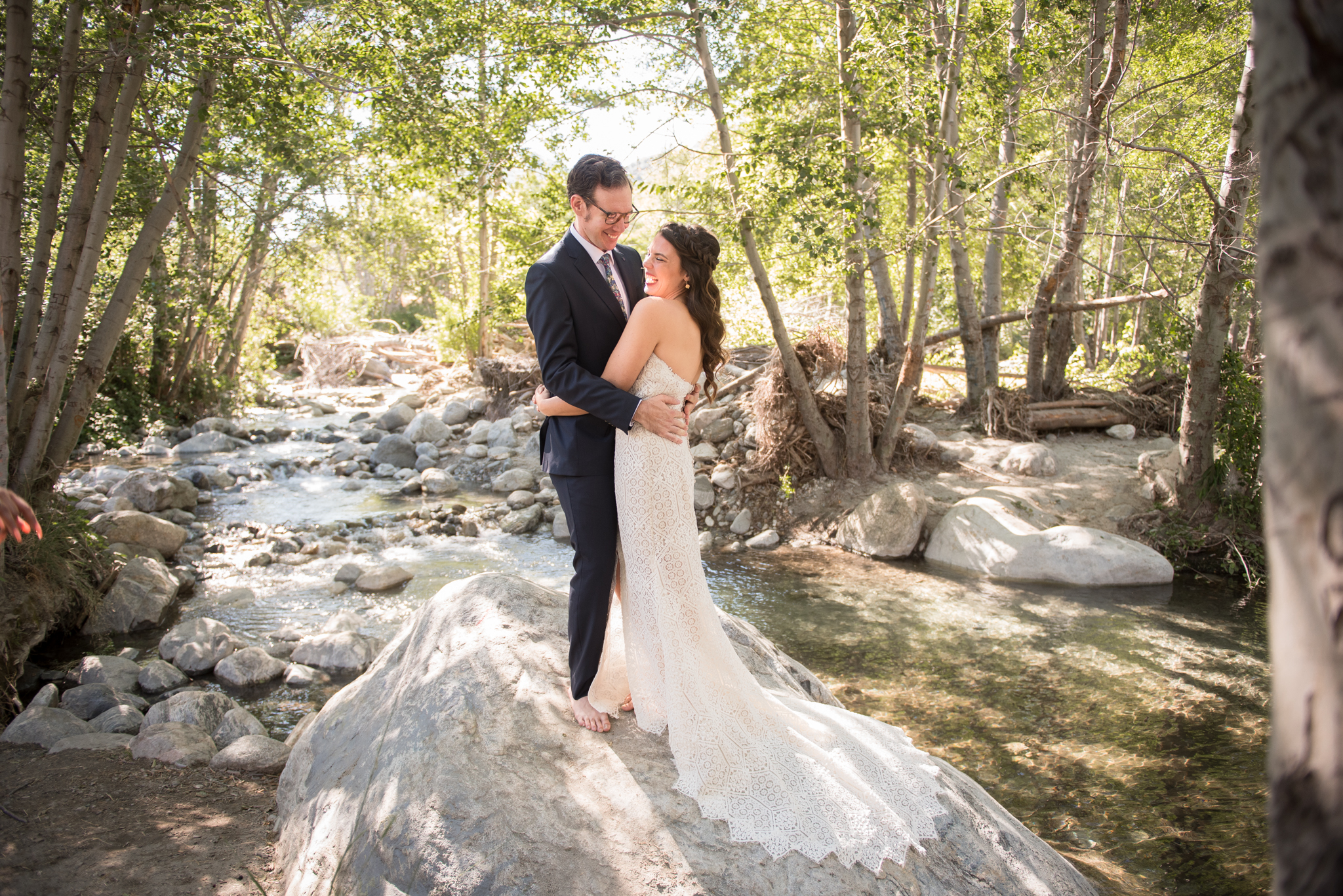 Bride and groom embrace on top of a rock at Thurman Flats California elopement