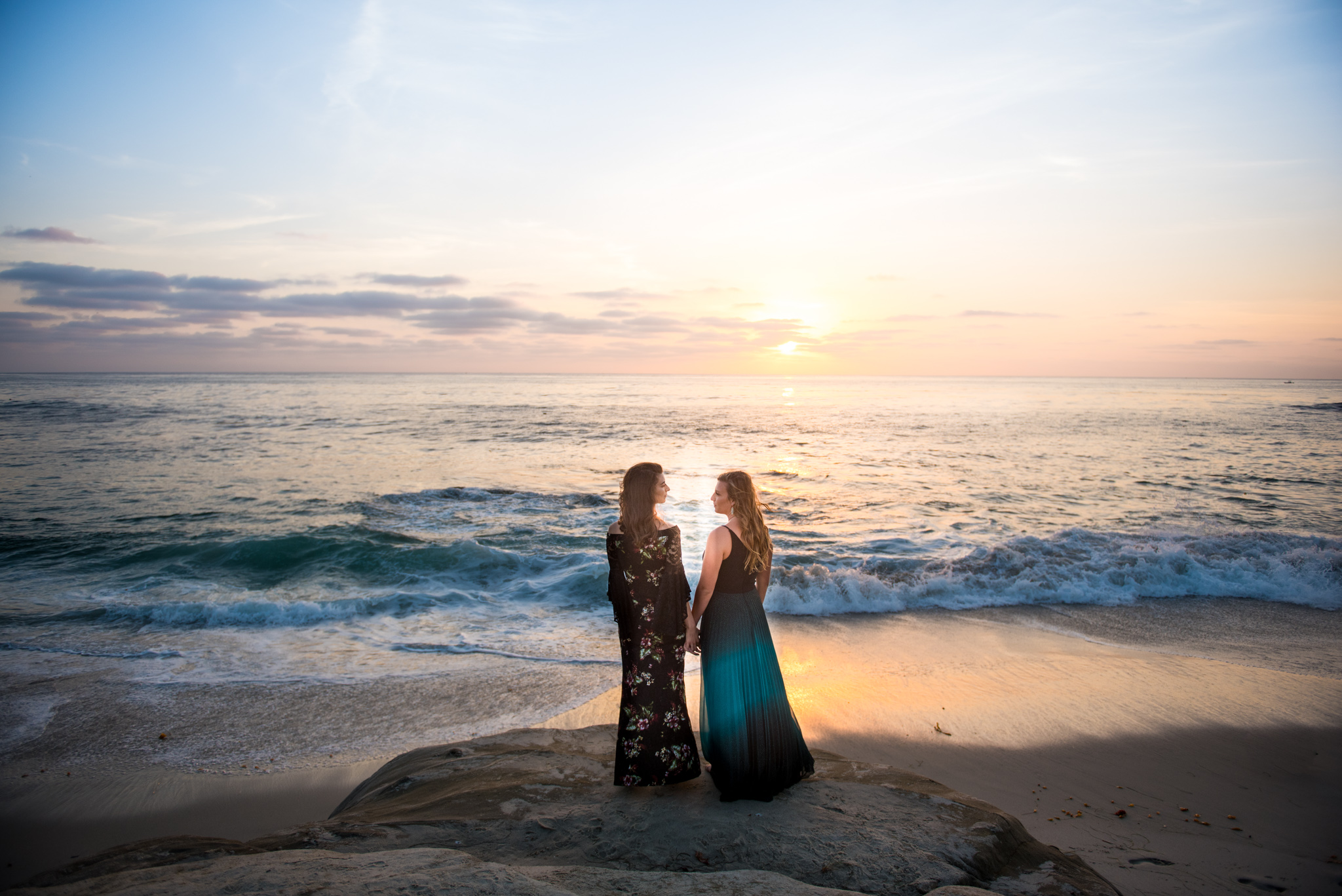 Two women face the ocean at sunset at Windansea Beach in San Diego engagement