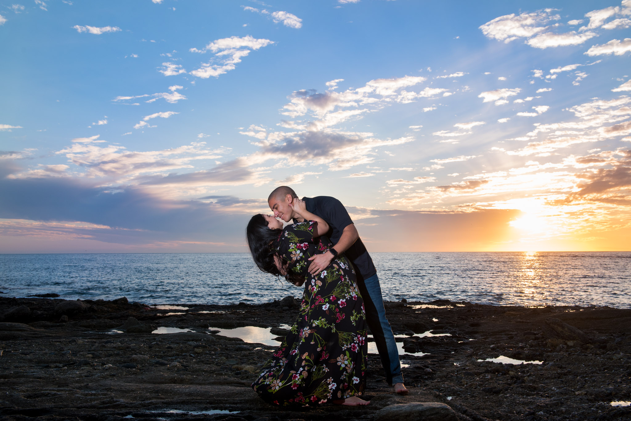 A man dips a woman in front of a sunset at Treasure Island Laguna Beach
